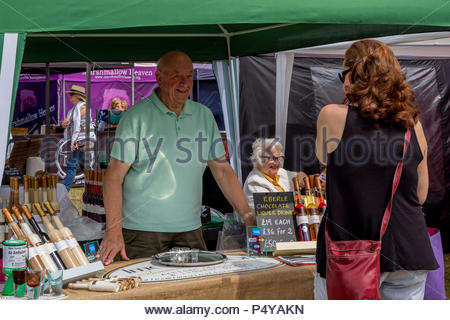 Visitors enjoying the sunshine at Fleet Food Festival 2018. Two smiling stallholders discuss their chocolate liqueur with a customer. - Stock Image