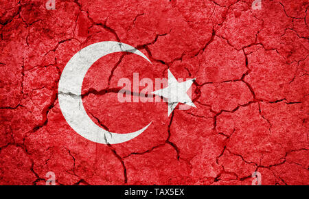 Republic of Turkey flag on dry earth ground texture background - Stock Image