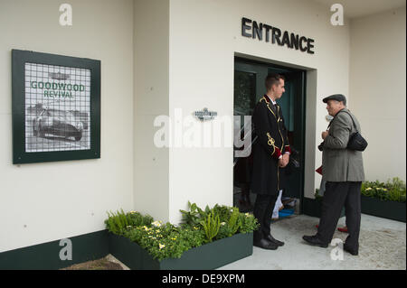 Chichester, West Sussex, UK. 13th Sep, 2013. Goodwood Revival. Goodwood Racing Circuit, West Sussex - Friday 13th September. A man enters the Earls Court Motor Show display and talks to the doorman on the way in © MeonStock/Alamy Live News - Stock Image