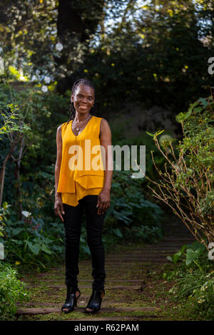 Elderly African woman standing on a garden path - Stock Image