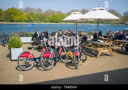 Tourists with Santander Boris bikes at the cafe by the Serpentine, Hyde Park, Londonggggg - Stock Image