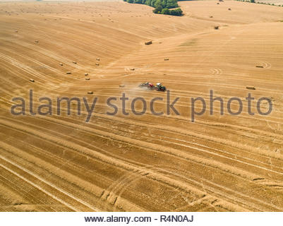 Aerial of tractor baler making straw bales in field after wheat harvest in summer on farm - Stock Image