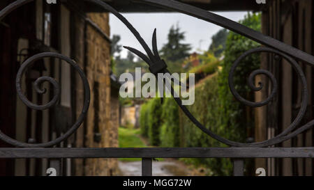 Intricate ornate wrought ironwork gates an alleyway between the ancient historic houses that front Moreton in Marsh's high street - Stock Image