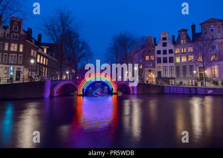 Amsterdam canal Herengracht during the Amsterdam Light Festival and bridge with artwork 'Bridge of the Rainbow' by Gilbert Moity. - Stock Image