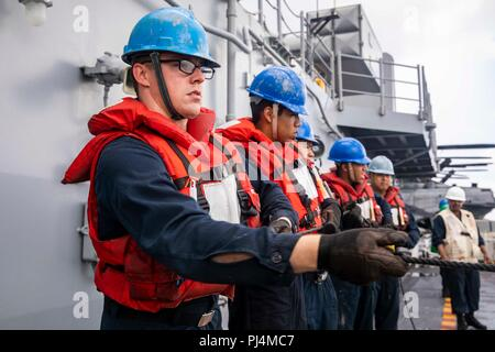 180830-N-JN023-0052 ATLANTIC OCEAN (Aug. 30, 2018) Sailors hold the phone and distance line to the fast combat support ship USNS Supply (T-AOE 6) during a replenishment-at-sea aboard the Wasp-class amphibious assault ship USS Kearsarge (LHD 3) as part of the Carrier Strike Group FOUR (CSG 4) Amphibious Ready Group, Marine Expeditionary Unit Exercise (ARGMEUEX). Kearsarge Amphibious Ready Group and 22nd Marine Expeditionary Unit are enhancing joint integration, lethality and collective capabilities of the Navy-Marine Corps team through joint planning and execution of challenging and realistic t - Stock Image