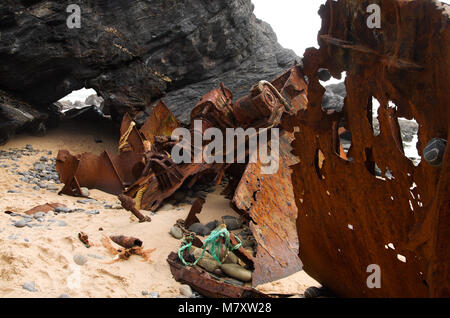 The bow of a pusher boat and some parts os the hull, completely rusted and withered by weather and sea, wrecked - Stock Image