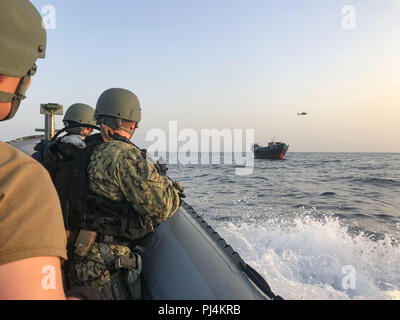 180828-N-N0146-6688 GULF OF ADEN (Aug. 28, 2018) visit, board, search and seizure team from the guided-missile destroyer USS Jason Dunham (DDG 109), approach a dhow during a flag verification boarding as part of maritime security operations. Dunham is deployed to the U.S. 5th Fleet area of operations in support of naval operations to ensure maritime stability and security in the Central Region, connecting the Mediterranean and the Pacific through the western Indian Ocean and three strategic choke points. (U.S. Navy photo/Released) - Stock Image