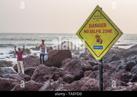 A sign warning visitors from shooting selfies on the rocks in this tropical location while people in the background are ignoring the same. - Stock Image