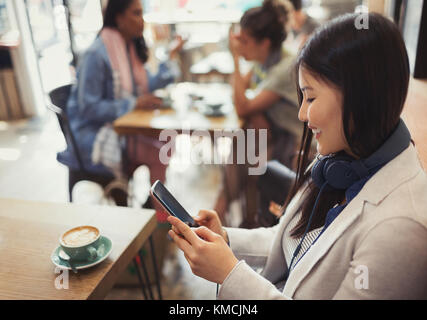 Smiling young woman texting with cell phone and drinking coffee at cafe table - Stock Image