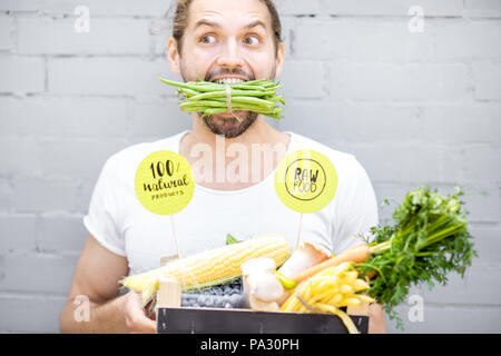 Portrait of a handsome man biting green beans standing with box full of fresh vegetables on the brick wall background - Stock Image
