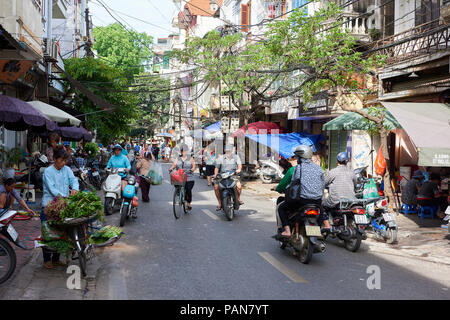 A traditional streert in Hanoi's Old Quarter, Vietnam, with street vendors, cyclists and moped riders. - Stock Image