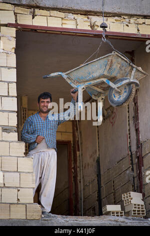 Welcoming Iranian construction worker with wheelbarrow. Shiraz, Iran - Stock Image