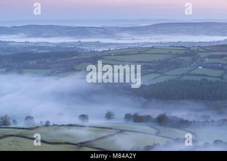 Misty rolling countryside at dawn, Dartmoor National Park, Devon, England. Winter (December) 2017. - Stock Image