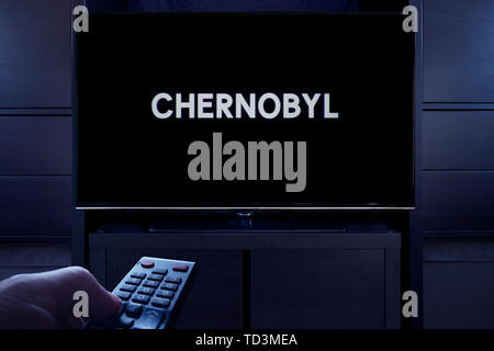 A man points a TV remote at the television which displays the Chernobyl main title screen (Editorial use only). - Stock Image