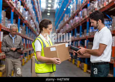 Female worker holding cardboard box while male worker scanning barcode - Stock Image