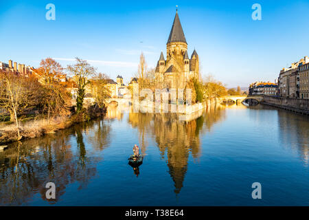 Metz, France - Jan 20 2019: Two amateur fisherman in an inflatable boat in center of Ville de Metz on Moselle river. Temple neuf - New Protestant chur - Stock Image