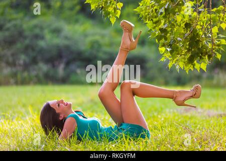 Beautiful teenager lying on greenfield in nature with legs holding in air upwards laughing very smiling young woman legs heels giggle giggling - Stock Image