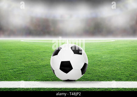 Soccer on football stadium field with blurred crowd background and copy space. - Stock Image