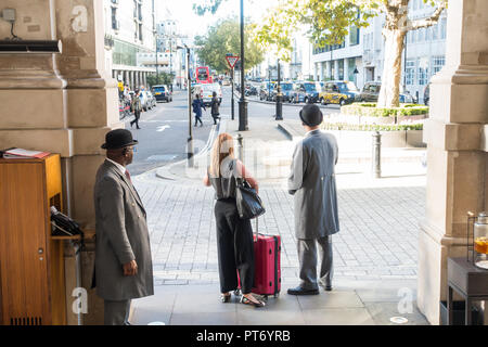 Doormen wearing bowler hats outside the Langham Hotel with a female guest waiting for a taxi, London, UK, Europe. - Stock Image