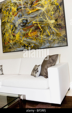 Couch and paintings in a living room - Stock Image