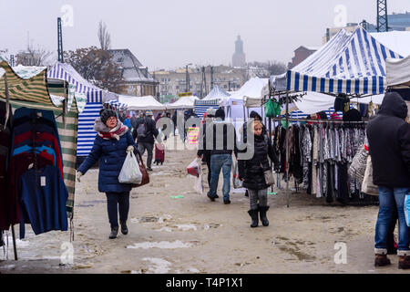 Customers walk through puddles and mud in an outdoor market, Wroclaw, Poland. - Stock Image