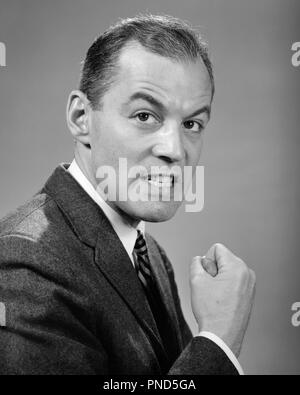 1950s 1960s ANGRY MEAN MAD BUSINESSMAN MAKING FIST LOOKING AT CAMERA  - p1666 HAR001 HARS MID-ADULT MAN RAGE RAISED EYEBROWS BLACK AND WHITE CAUCASIAN ETHNICITY HAR001 OLD FASHIONED - Stock Image