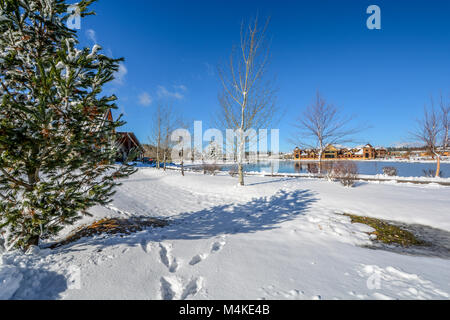 Picturesque setting in the mountains of the Pacific Northwest with a frozen pond on a sunny day with winter snow - Stock Image