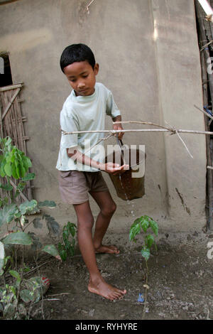 BANGLADESH Boy of the Garo tribal minority watering plants in his parents' garden, Haluaghat, Mymensingh region photo by Sean Sprague - Stock Image