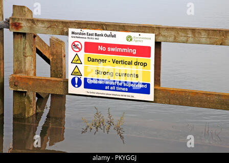 A warning sign by the Norfolk Coast Path by salt marshes at Morston, Norfolk, England, United Kingdom, Europe. - Stock Image