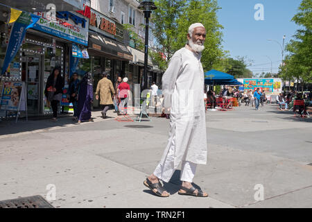 A Muslim man in traditional ethnic dress walking in Diversity Plaza in Jackson Heights, Queens, New York - Stock Image