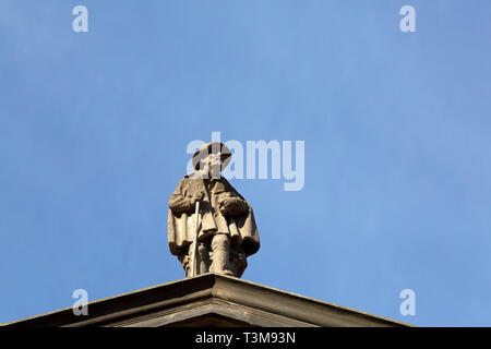 Sculpted figure of an aged man in Haarlem, the Netherlands. The figure is on the roof of the Frans Hals Museum. - Stock Image