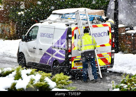 Winter weather snowy street scene snowflakes around BT Openreach van & engineer high vis jacket working with ladder in falling snow storm England UK - Stock Image