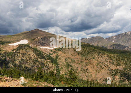 Sunny, largely bare Colorado Rocky Mountains, with dominant pointed peak on left. Patches of snow. Slightly dark clouds above.  Good for background. - Stock Image