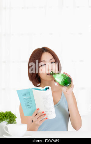 Young woman drinking and reading a book, - Stock Image