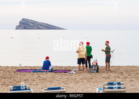 Benidorm, Costa Blanca, Spain, 25th December 2018. British tourists dress for the occasion on Christmas Day in this favourite getaway destination for Brits escaping the cold weather at home. Temperatures will be in the mid to high 20's Celsius today in this mediterranean hotspot. People on beach wearing santa hats and christmas jumpers with the sea and Peacock Island in the background - Stock Image