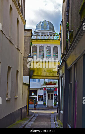 A small side street in Tenby.The glass sided bridge dates back to the premises of T P Hughes, a local fashion & homeware shop, now moved. - Stock Image