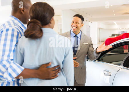 friendly car dealer showing new car to customers - Stock Image