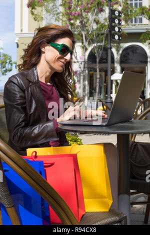 brown hair woman with red shirt, leather blazer and sunglasses sitting at urban cafe terrace outdoors, at street, with shopping bags typing in compute - Stock Image