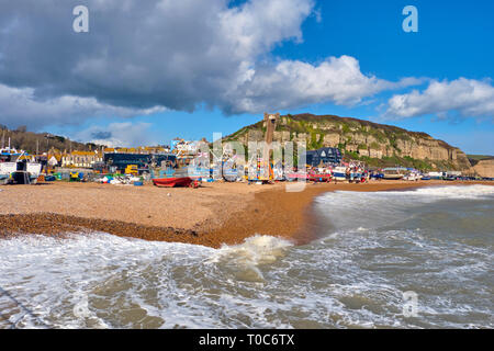 Hastings, East Sussex, UK. 10th March 2019. Hastings fishing boats pulled up high on the Stade beach out of reach of waves driven by gale force winds - Stock Image