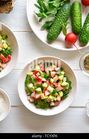 Healthy vegetable salad from avocado, radish, cucumber, greens in bowl over light wooden background. Organic natural or vegetarian vegan food concept. - Stock Image