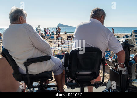 Benidorm, Spain. 30 December 2018. British tourists mix with locals on the beaches and in the bars and restaurants as they escape the cold British weather and head south to Spain. High temperatures meant that the beaches were busy from early morning with families enjoying the calm sea and temps of about 17 Celsius. middle aged couple sitting an a disability scooter on the promenade in this popular Spanish resort. Credit: Mick Flynn/Alamy Live News - Stock Image