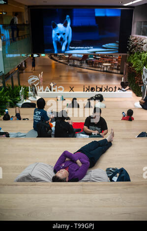 18.04.2019, Singapore, , Singapore - People rest in front of a video screen in Terminal 3 at Changi International Airport. 0SL190418D030CAROEX.JPG [MO - Stock Image
