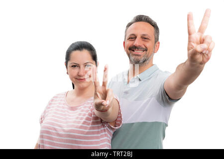 Smiling couple making peace or victory sign with index and middle fingers isolated on white studio background - Stock Image