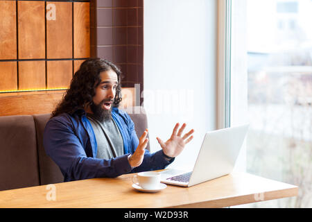 No way! Shoched handsome young adult man freelancer in casual style sitting in cafe and dont save changes of report in laptop, showing hand to noteboo - Stock Image