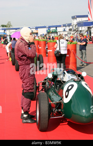 Racing driver getting into his car - Stock Image