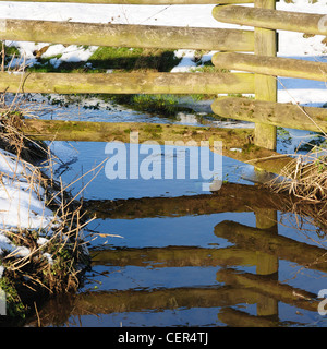 Fence reflected in stream near the north Oxfordshire village of Hook Norton after snowfall - Stock Image