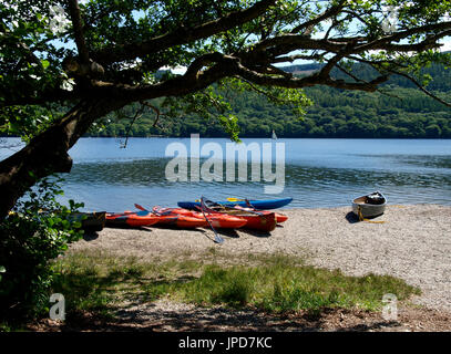 Canoes on the edge of Coniston Water, The Lake District, Cumbria, UK - Stock Image