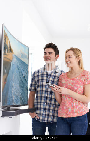 Young Couple With New Curved Screen Television At Home - Stock Image