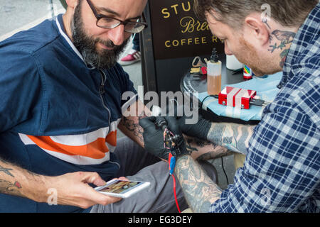 Tattoo artist Alex McWatt of Three Kings Tattoo applying a tattoo to the arm of a man who is checking his cellphone - Stock Image