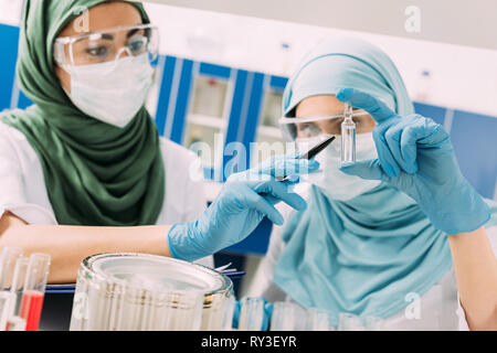 female muslim scientists in medical masks holding glass ampoule during experiment in chemical laboratory - Stock Image